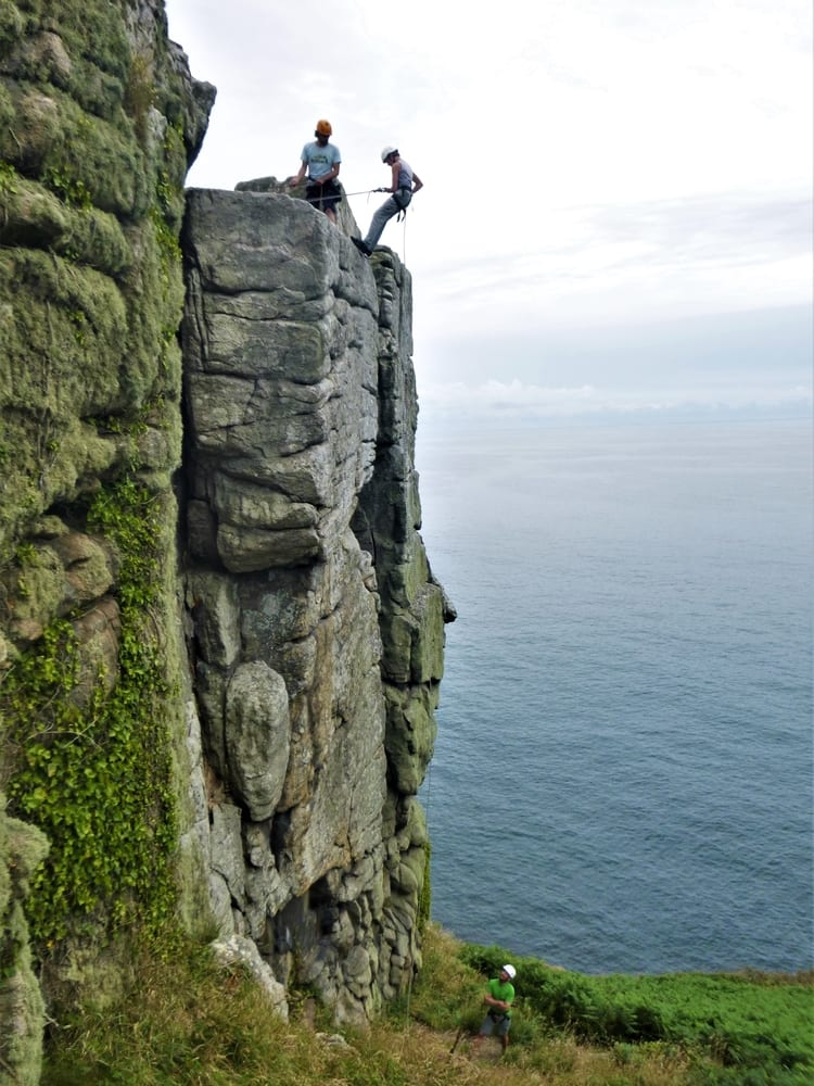 Learn abseiling and other essential rock climbing skills in Cornwall with Kernow COasteering. Here ciber abseils down a cliff in