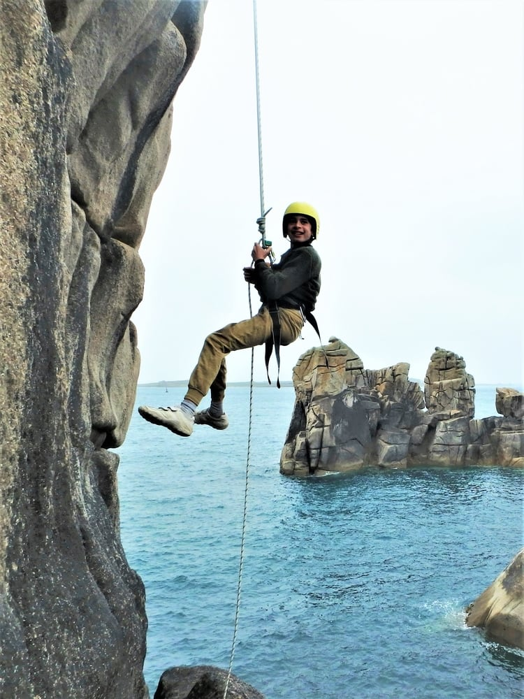 Young rock climber abseiling down a sheer cliff with Kernow Coasteering on a beginner rock climbing course in Cornwall