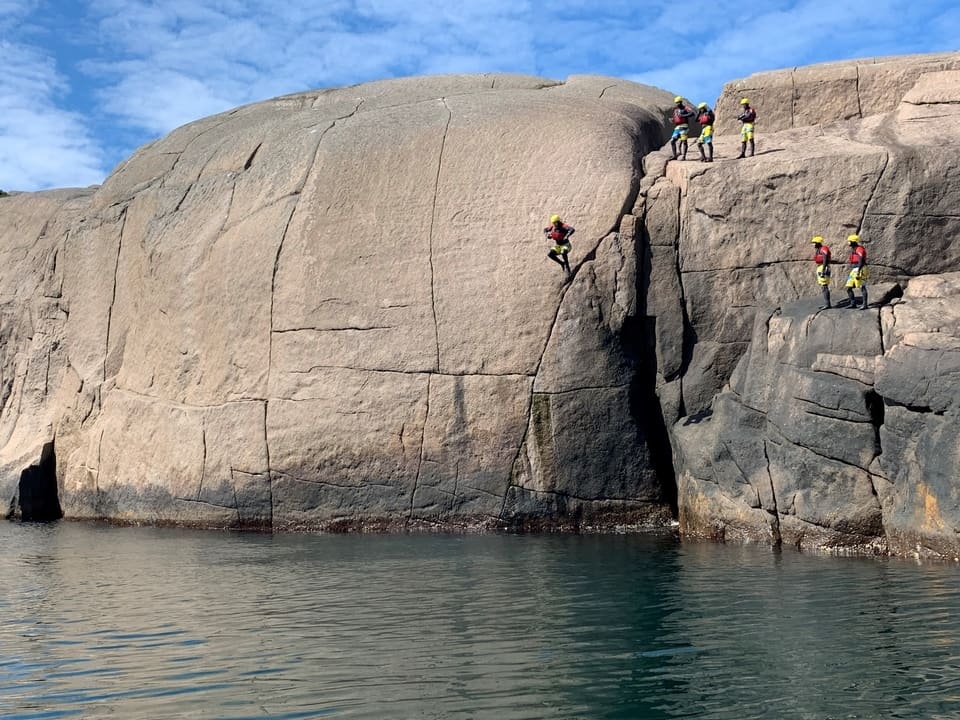 Large cliff jump coasteering in Norway in the Unesco Magma coastal Geopark.