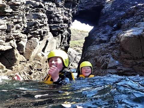 Two young people go through a sea arch in Cornwall on a beginner coasteering trip at Praa Sands with Kernow Coasteering