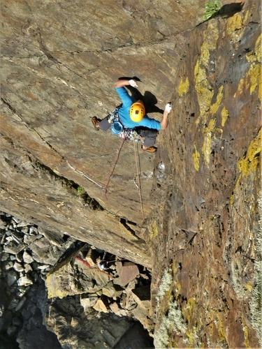 Kernow Coasteering climbing instructor leading Thane, E1, at Kenidjack Cliff, Cape Cornwall, UK.