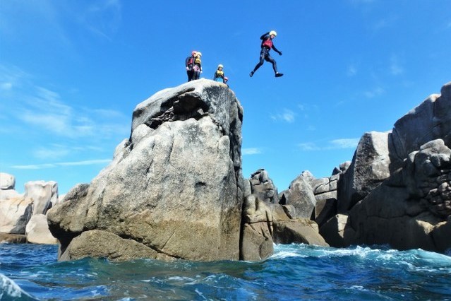 Amazing coasteering scenery at Peninnis Head, Isles of Scilly, as a coasteering group member jumps of a high cliff..