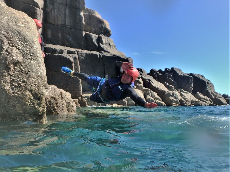 Diving into the water whilst coasteering at Land's End in Cornwall