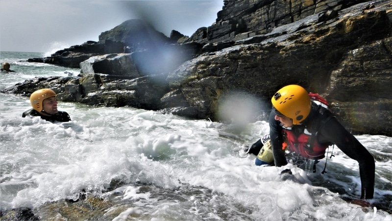 Coasteering at Praa Sands, exiting up a slippery slab in Cornwall.