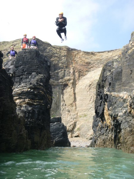 Coasteerer jumping with excellent style into a gully at Praa Sands, Cornwall with Kernow coasteering.