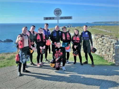 Coasteering group at Land's End landmark signpost having completed Cornwall's ultimate coasteering adventure with Kernow Coastee