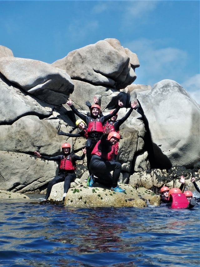 Coasteering group gathered in a rock on the isles of Scilly at Peninnis Head
