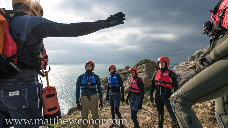 Kernow Coasteering guide gives a group safety briefing before beginning a coasteering session in Cornwall