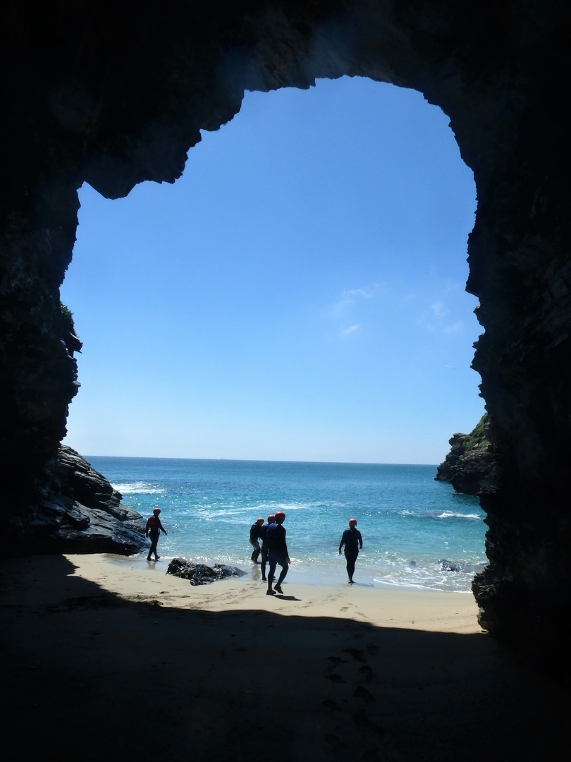 Coasteering Cornwall. A group explores a large Sae Cave at Prussia Cove, Penzance