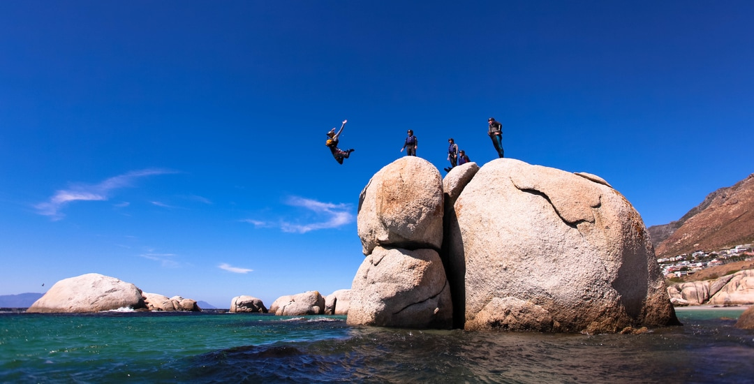 Amazing cliff jump from a giant granite boulder, coasteering with gravity Adventures, South Africa.