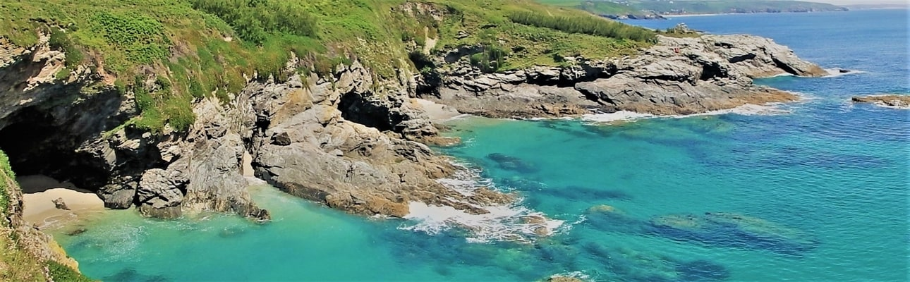 Prussia Cove caves with Praa Sands in the background. Photo by Kernow Coasteering