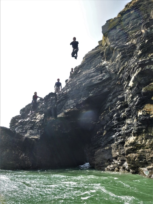 Cliff jump at Praa Sands, near Porthleven and Penzance in Cornwall. COasteering with Kernow Coasteering