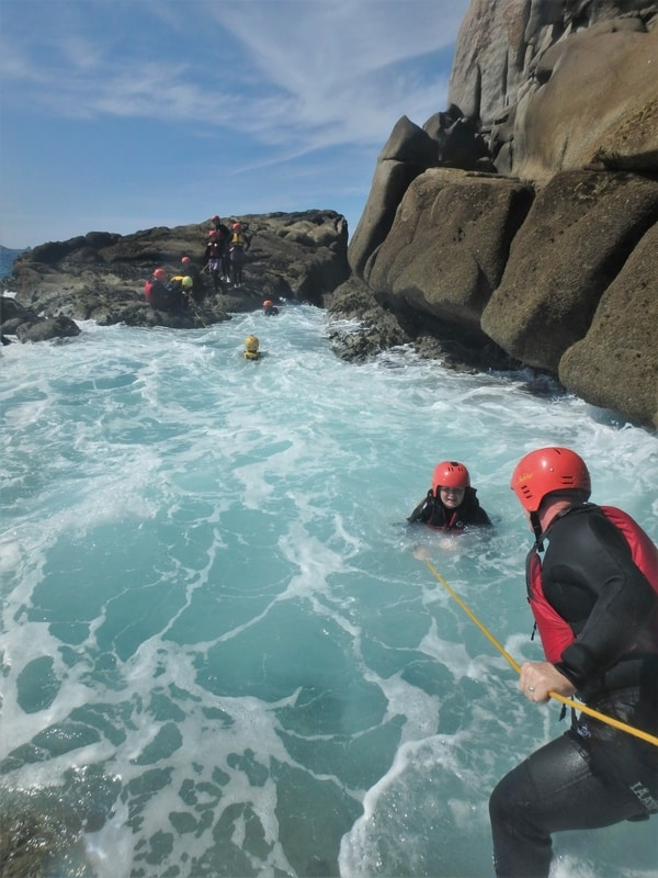 Crossing a gully in rough conditions whilst coasteering on the isles of Scilly