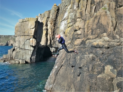Coasteering at Land's End. Large cliff jump near the First and Last House, Land's End, Cornwall, UK./