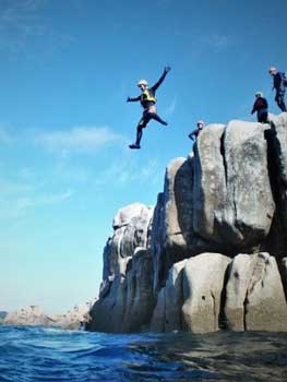 Kernow Coasteering guide jumping at Peninnis Head, Isles of Scilly. Cornwall and Isles of Scilly's best coasteering