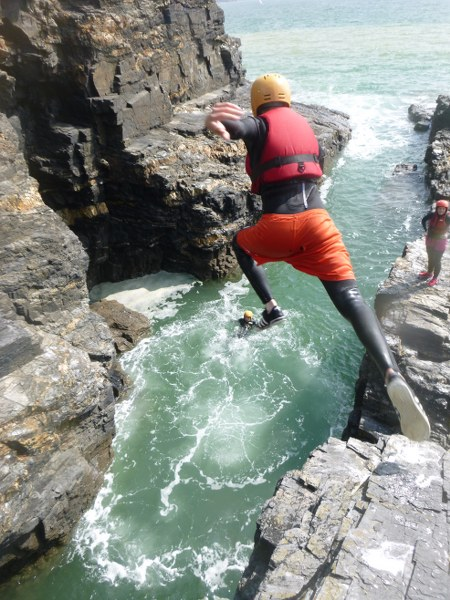 Kernow Coasteering group member jumping into a gully near Praa Sands, west Cornwall, UK.
