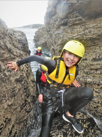 Coasteering is suitable for all ages and abilities. Here a young boy is coasteering with Kernow Coasteering in Cornwall.