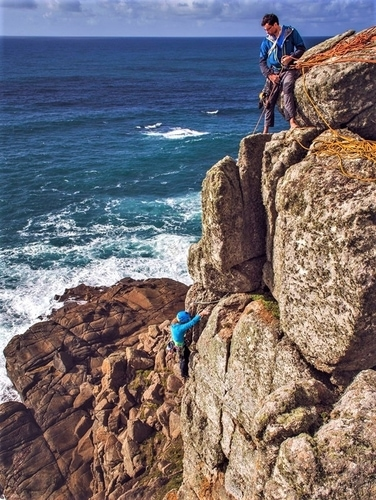 Climbers on a multi pitch rock climb at Carn Barra near Porthcurno and Land's End. Rock climbing instructors from Kernow Coastee