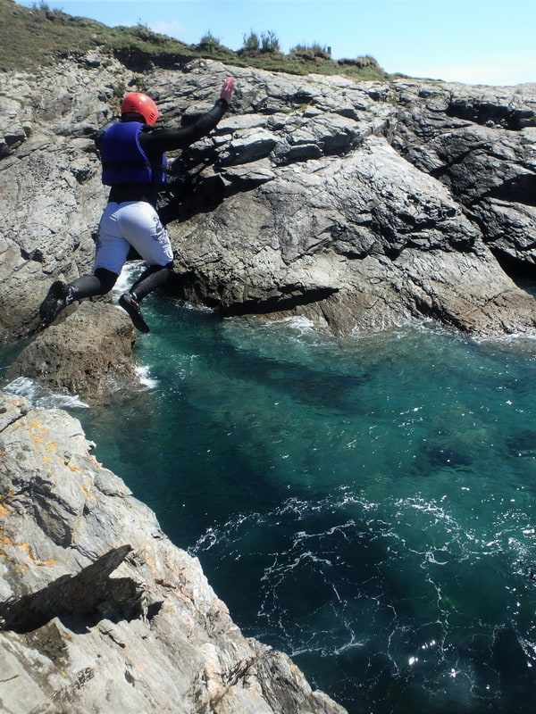 Coasteering at Prussia Cove, near Penzance, Cornwall. Here coasteerer does a large jump into crystal blue waters.
