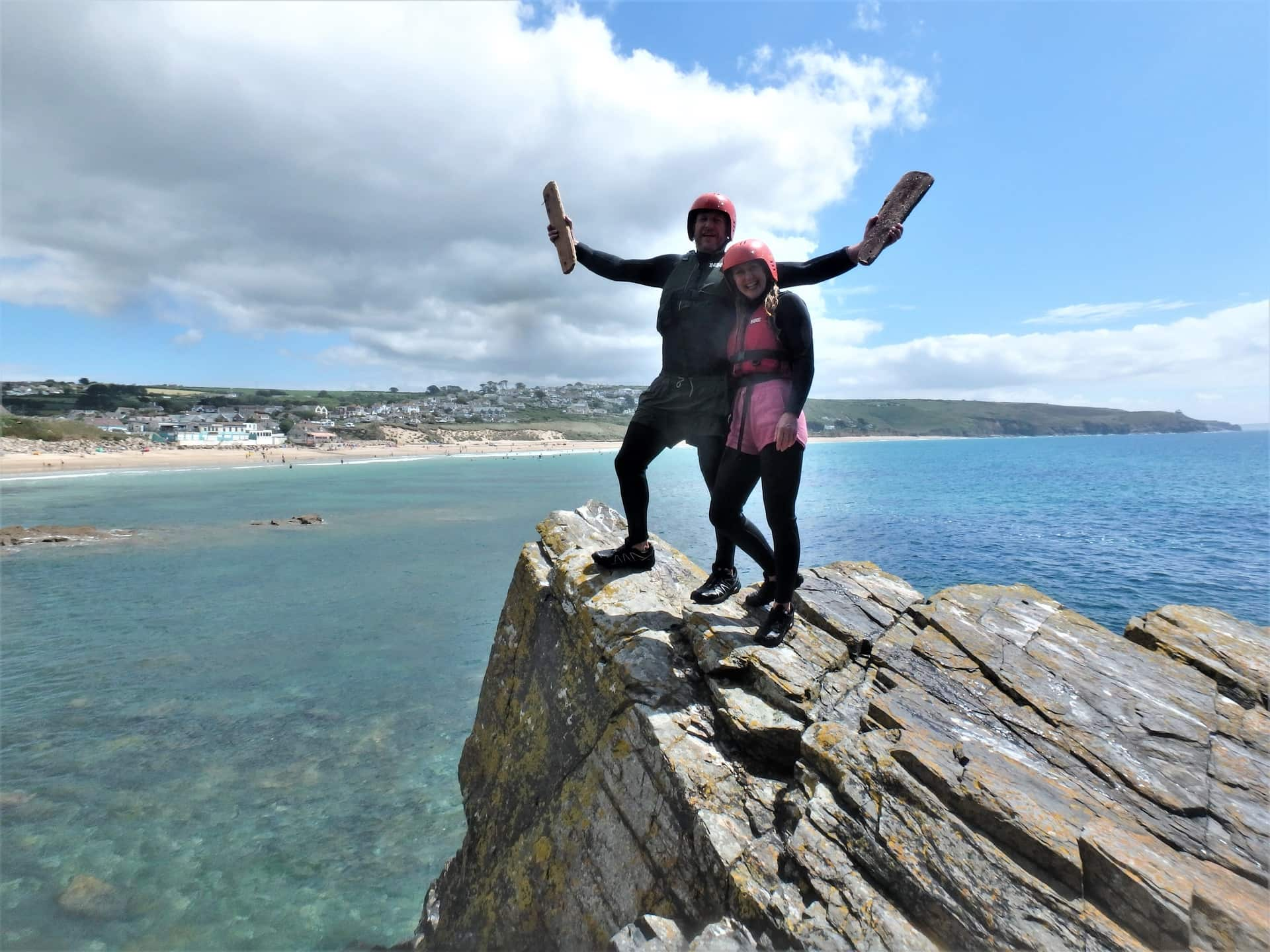 Couple posing at Praa Sands after a session with Kernow Coasteering. Praa Sands and Rinsey Head in the background.