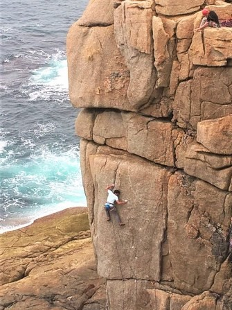Kernow Coasteering climbing instructor leading Demolition, E6 at Sennen, Cornwall.