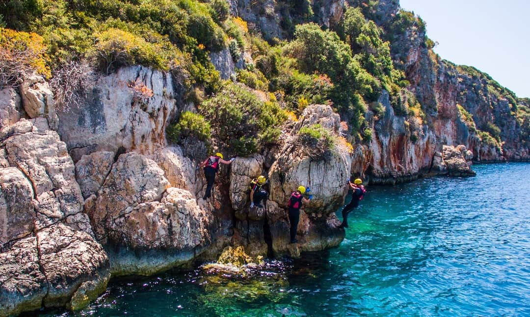 Group traversing along limestone cliffs whilst coasteering in Turkey with Dragoman