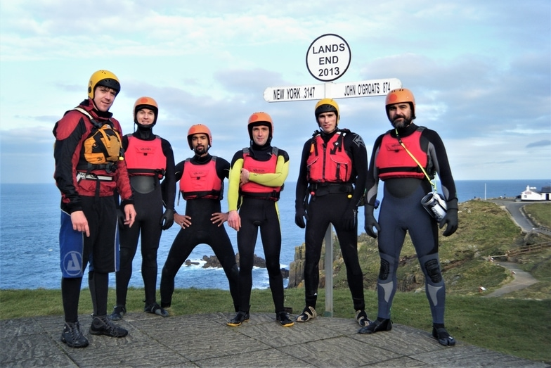 Group gathered at the iconic Land's End signpost after exploring coasteering at the end of Cornwall.