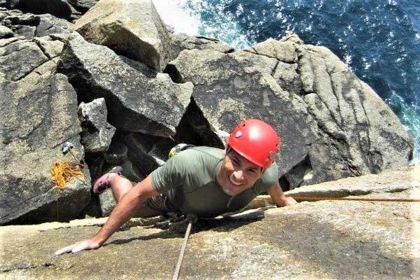 Rock climber at Sennen, Cornwall, on the climb Catholic Girls. Rock climbing courses with Kernow Coasteering