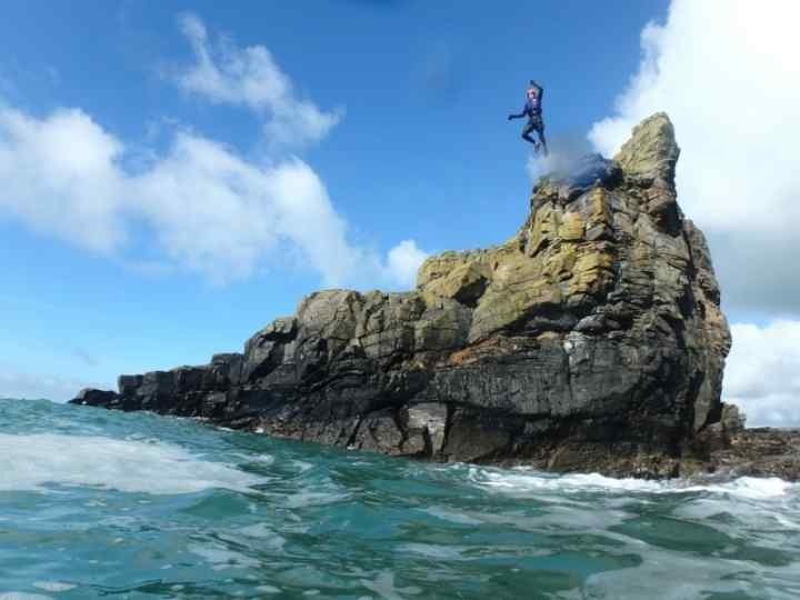 Large cliff jump during a coasteering session with Kernow Coasteering in Cornwall, at Praa Sands near Porthleven and Penzance.