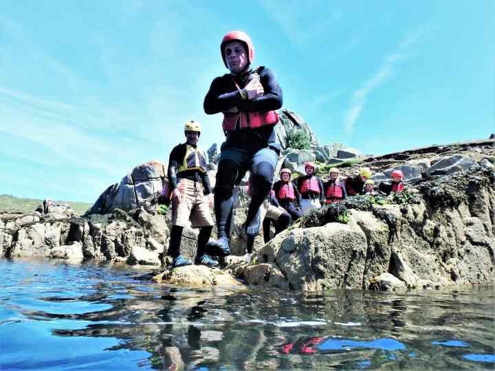 Start of a coasteering session on Isles of Scilly. Coasteering group at St. Mary's jumping into water at Peninnis Head. Best act