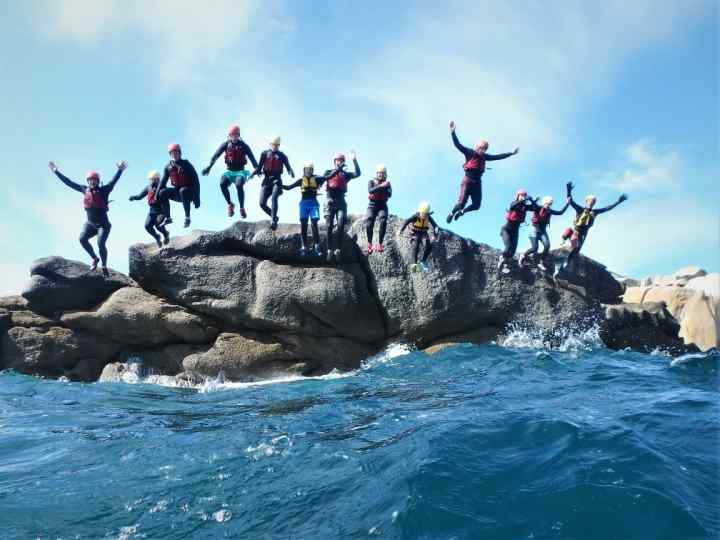 Large group party jump at Peninnis Head with Scilly and Cornwall's best coasteering, Kernow Coasteering