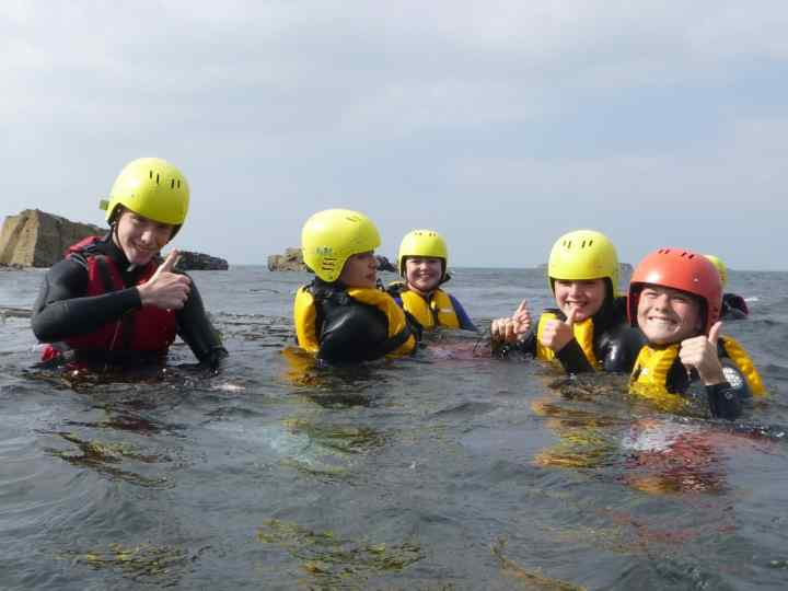 Cornwall's best adventure day's out. Activities for all the family. Here a group of young people are enjoying coasteering near S