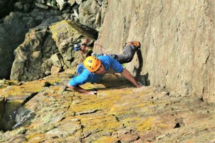Kernow Coasteering climbing instructor rock climbing near Cape Cornwall, St. Just, Cornwall. Kendijack Cliff, the route is Thane