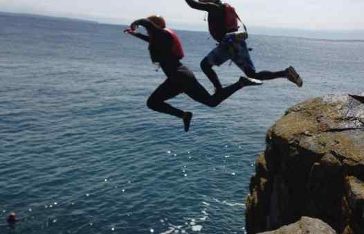 Two people coasteering, jumping off a large jump at Prussia Cove together.