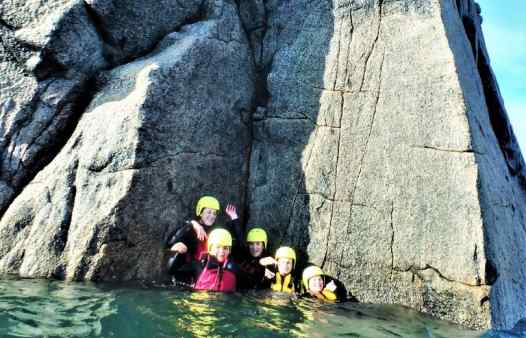 Group gathered a sunken ledge coasteering at Peninnis Head, St. Mary's