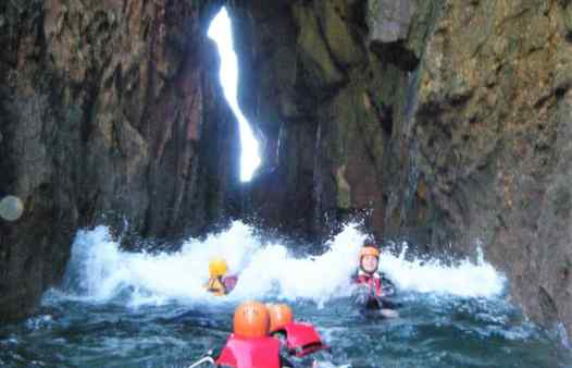 Group getting washed through an archway by a wave coasteering in Cornwall with Kernow Coasteering
