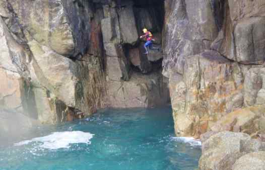 Breathtaking cliff jump in front of a giant sea cave with Kernow Coasteering at Land's End, Cornwall