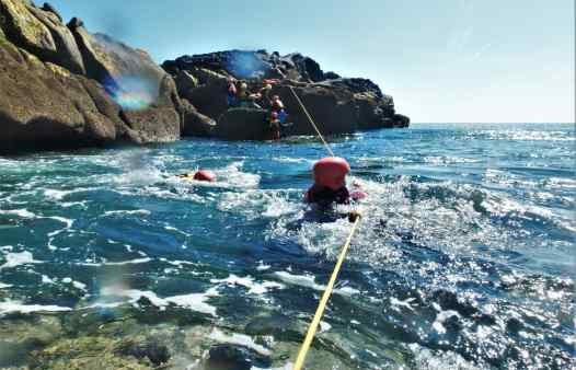 Kernow Coasteering guides using ropes to cross a choppy gully