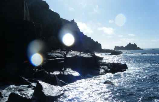 Stunning sunlit scene below the cliffs at Land's ENd. Discovering the secrets of COrnwall with Kernow Coasteering.
