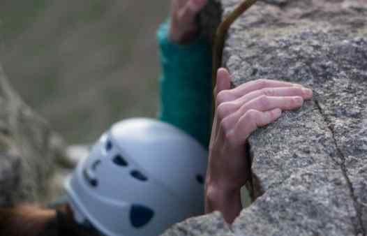 Climber at Trewavas in Cornwall, close up of fingers pulling hard on a rock hold.