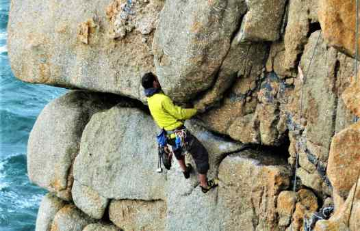 Rock climber on the crux of Demo Route at Sennen, Cornwall