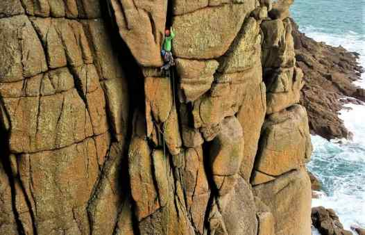 Climber enters the giant crack of Sea Horse, rock climbing in Cornwall.
