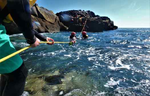 Coasteering guides set up a rope to help group cross rough sea on the Isles of Scilly